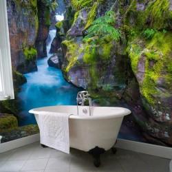 Rivière bleue traverse les rochers tapissés de mousse verte